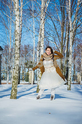 Beautiful bride on a sunny winter day behind the birch. snowy weather. blye sky and trees on the background. Girl in a short wedding dress, rustic style