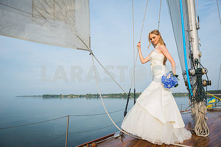 Beautiful blonde bride in a long white dress poses on a sailing yacht at sea with the blue bouquet in her hand and the other hand on the rope on a sunny day