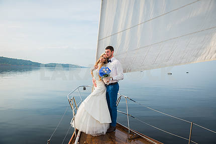 Honeymoon sailing - Stylish young bride and groom standing on the nose of board the sailing yacht