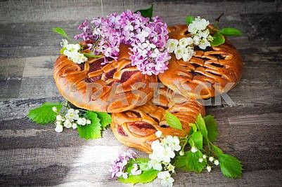 Strawberries and blackcurrant pie with jam, decorated with spring flowers