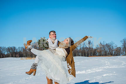a lovely wedding couple  - husband holds the wife on hands. rustic style. stylish wedding. cold sunny day. happy couple - winter background.