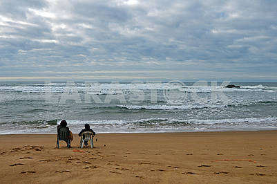 A couple siting on the beach Praia de Odeceixe in South Portugal