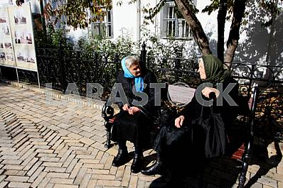 The parishioners are talking on the bench in the Kiev-Pechersk Lavra. Feast of the Intercession of the Holy Virgin