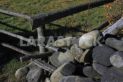 Large oval stones under the fence