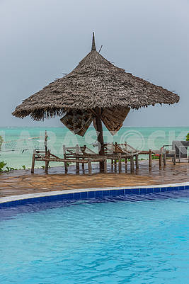 Straw umbrellas and chaise lounges on the beach