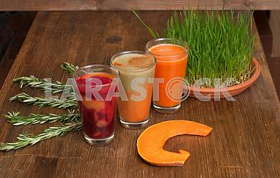 Various freshly squeezed vegetable juices with the hunk of pumpkin and germinating wheat on a wooden table.