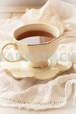Tea in a white pot of a cup on a white vintage napkin background, vertical image