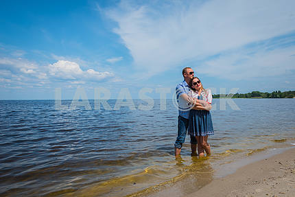 a loving couple standing in the river, embracing each other, blue sky on the background, sunny day, wide angle, long white clouds