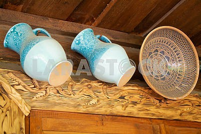 Ceramic glazed blue jugs and traditional clay bowl on wooden background.