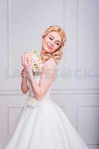Blonde beautiful bride in short dress with wedding bouquet