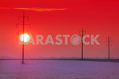 Sunset on the background of electric poles