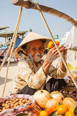 Grandmother, a saleswoman of fruit sitting near the basket