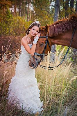brown-haired woman standing leaning to the horse, in wedding dress mermaid silhouette, among the spikelet, autumn, forest on the background