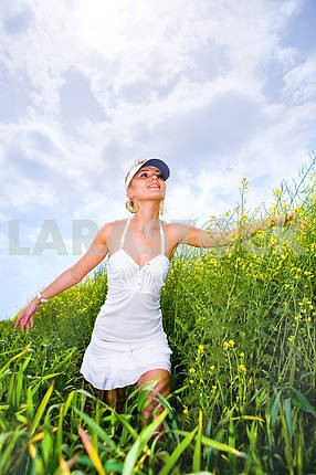 Happy young woman is walking in a yellow field