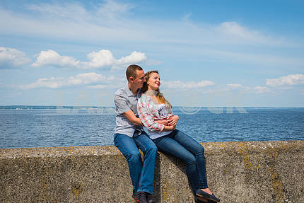 couple in love embracing, sitting together, holding with the hands, near the water on a sunny day, blue sky with long white clouds on the background. men and women are  smiling, happy