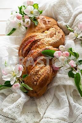 Fresh baked sweet braided yeast bun, wicker russian loaf with spring flowers