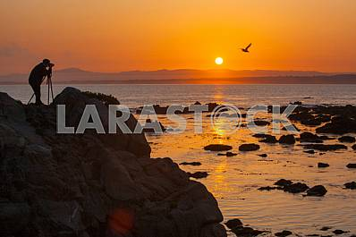 Photographer is macking photos of sunrise  on the shore of the Pacific ocean
