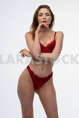 Young beautiful girl pose in studio in red lingerie