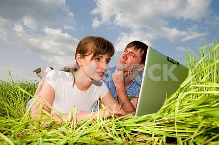 Casual happy couple are talking  and laughing on a laptop comput