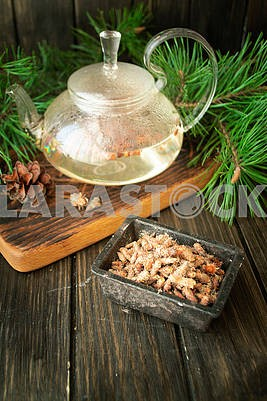 Tea pot of herbal tea with pine buds on wooden background
