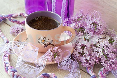 Violet cup of morning coffee or cappuccino and delicate pink, purple, lilac flowers. Mother's day concept. Cozy breakfast