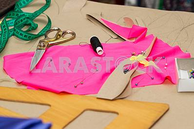 Scissors, reel of thread, measuring tapes and natural fabric. Sewing textile or cloth. Work table of a tailor. Textile tools. Copy space. Top view