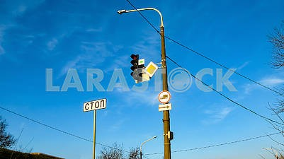 Traffic light and road signs on a blue sky background