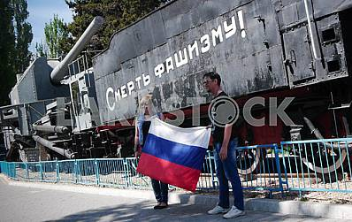 """People posing with the Russian flag against the background of the artillery train """"Zheleznyakov"""" in Sevastopol."""