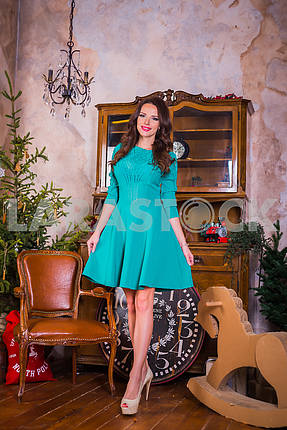 Beautiful brunette woman walking,  among the new year decorations in bright blue dress, smiling