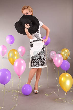 Beautiful young girl in light dress a hat on background balloons