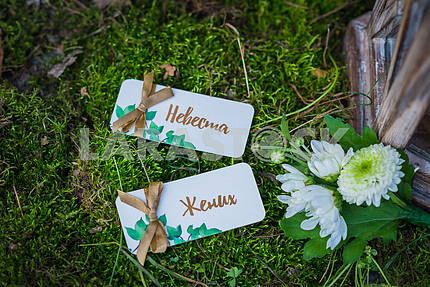Wedding decorations - written on russian bride and groom on the vintage paper, and the boutonniere laying - flat lay. Vintage wooden lantern and moss on the background