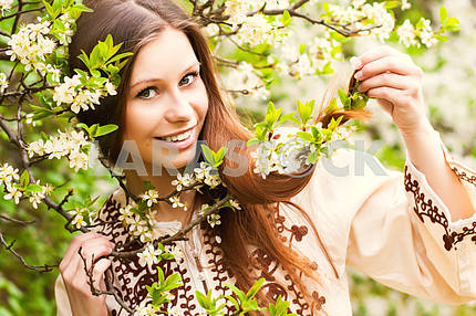 Portrait of a beautiful spring girl in cherry tree flowers.