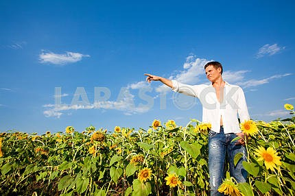 Happy young man shows the direction of hand