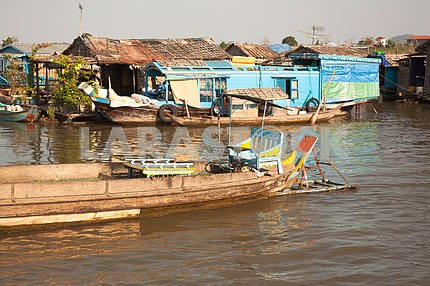 Boat with original seat and the steering wheel of a car, moored to the house on the water in Lake Tonle Sap in Cambodia.