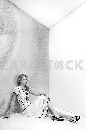Beautiful girl in white dress sitting on the floor. In black sho