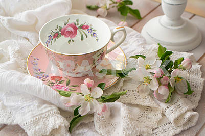 Pretty pink vintage afternoon tea party, tea cup and tender flowers on wooden tray and lace tablecloth