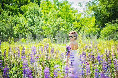 Young woman, happy, standing among the field of violet lupines, smiling, purple flowers. Blue sky on the background. Summer, sunny day, tuning back with bouquet