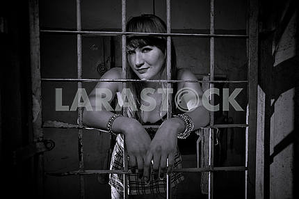 Young girl closed behind bars, grid, like in prison. looking sexy in short skirt