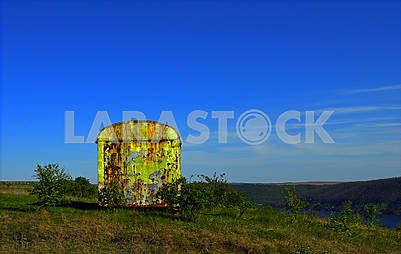 Iron rusty container on the meadow