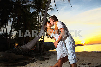 young loving couple hugging on beach at sunset