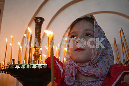 A girl holding a candle during a liturgy