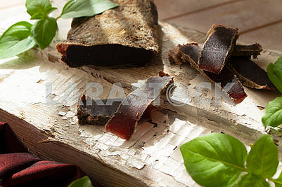 dried roe deer meat on a rustic shabby cutting board