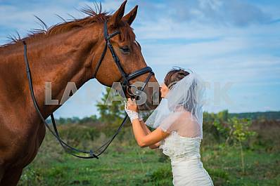 Bride portrait of brown-haired woman standing in front of a horse and kissing, in wedding dress mermaid silhouette, blue sky on the background
