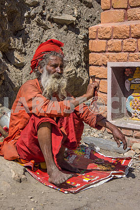 The sadhu is holding the pipe
