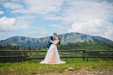 Romantic fairytale couple newlyweds kissing and embracing on a background of mountains. wedding walk on nature, Newlyweds outdoors portrait, soft light, series