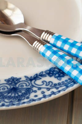 White and blue round plate with utensils on blue wooden table background