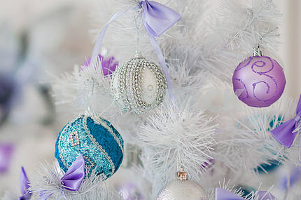 Closeup of Christmas - tree decorations . Silver background . blue toy on a white Christmas tree, with white and violet toys, one style decorated. New Years  ball  - globe