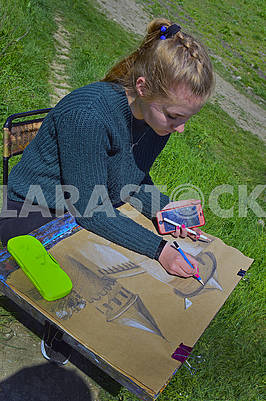 Young girl draw on a plein air