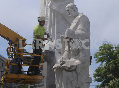 A cleaning company employee washes a monument to Cyril and Methodius