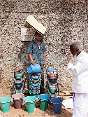 The seller of plastic buckets on the street